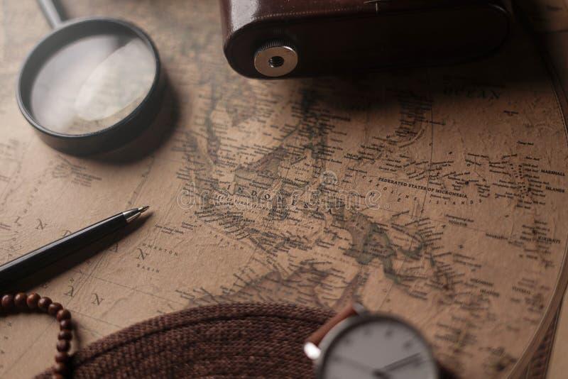 Mapa de Indonésia entre os acessórios do viajante no mapa velho do vintage Fundo do conceito do curso fotos de stock royalty free