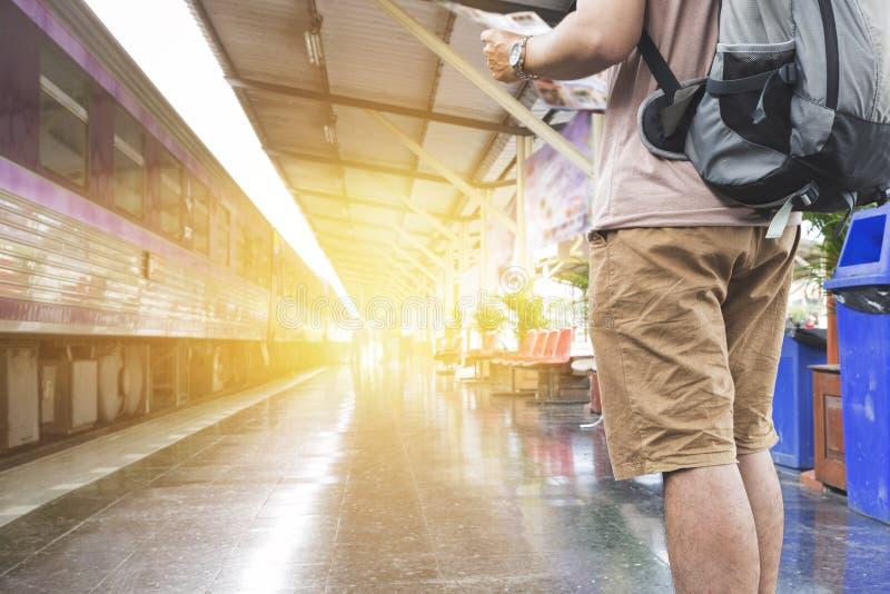 mapa de la tenencia del hombre con la mochila en la estación de tren fotografía de archivo