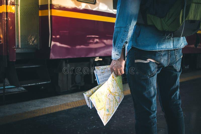 Mapa de la tenencia del hombre joven que se coloca en la plataforma en la estación de tren para el viaje foto de archivo