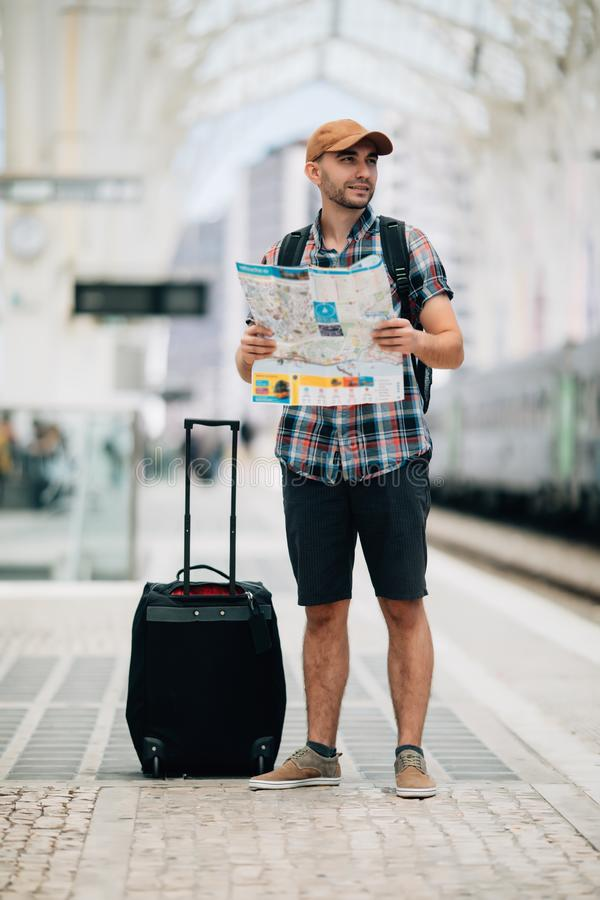 Mapa de la tenencia del hombre joven que se coloca en la plataforma en la estación de tren para el viaje Concepto del viaje en tr imagenes de archivo