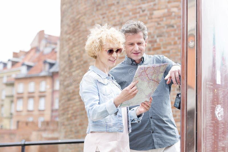 Mapa de meia idade de sorriso da leitura dos pares na cidade fotografia de stock