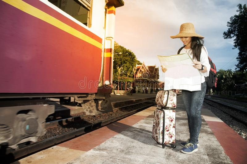 Mapa de mirada femenino del viajero bastante asiático y tren que espera foto de archivo