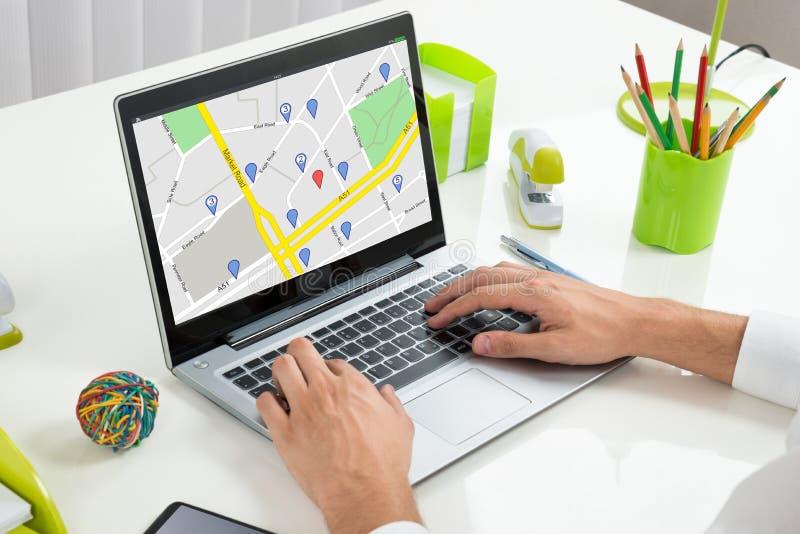 Mapa de Person Using GPS en el ordenador portátil fotos de archivo