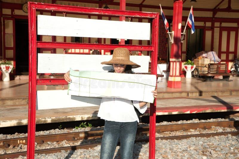 Mapa de vista fêmea do mochileiro asiático bonito do viajante na estação de trem foto de stock