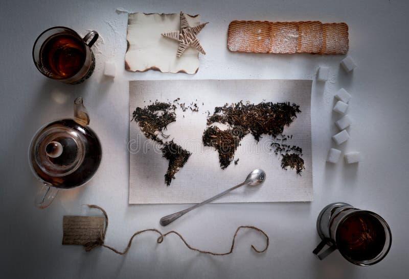 Mapa del mundo, alineado con las hojas de té Eurasia, América, Australia, África vendimia azúcar, nota, galleta, cuchara tapa fotografía de archivo