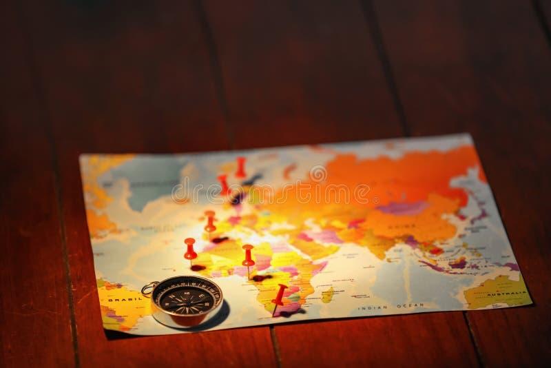 Mapa del mundo con el compás y los pasadores en la tabla fotos de archivo libres de regalías