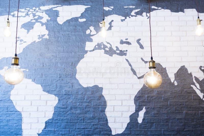 Mapa del mundo en la pared de ladrillo con la bombilla, la decoración moderna o el diseño interior imágenes de archivo libres de regalías