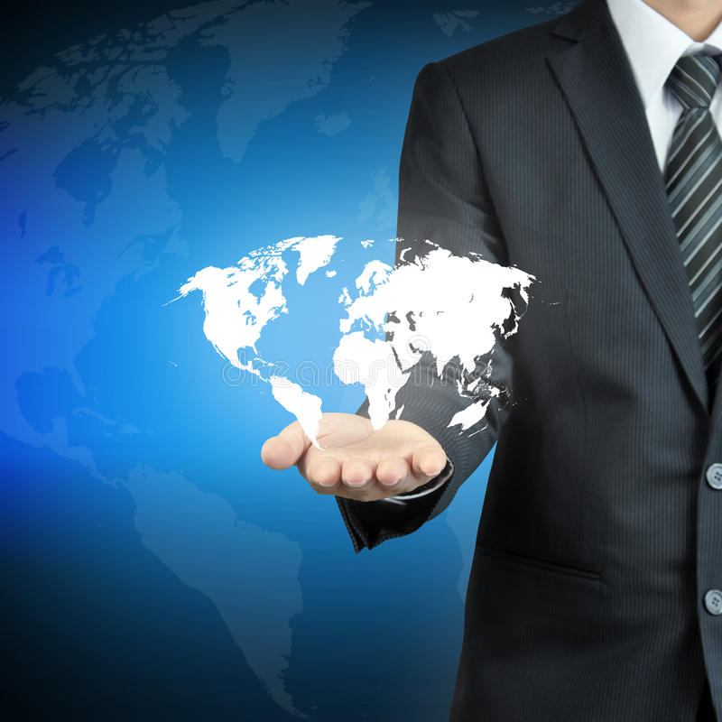 Mapa del mundo que lleva de la mano del hombre de negocios imagen de archivo