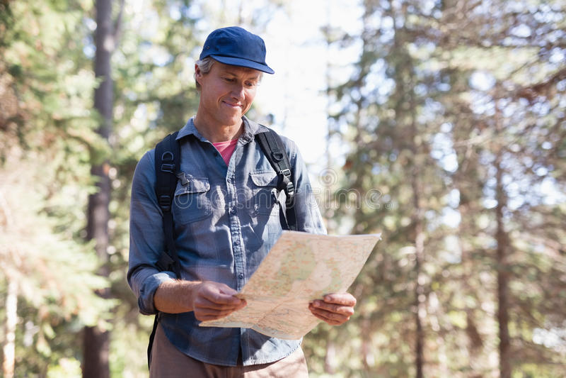Mapa feliz de la lectura del caminante en bosque fotos de archivo libres de regalías