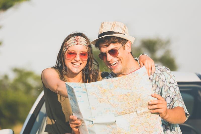Mapa joven hermoso de la tenencia de los pares al aire libre Concepto de las vacaciones de verano del viaje por carretera imágenes de archivo libres de regalías