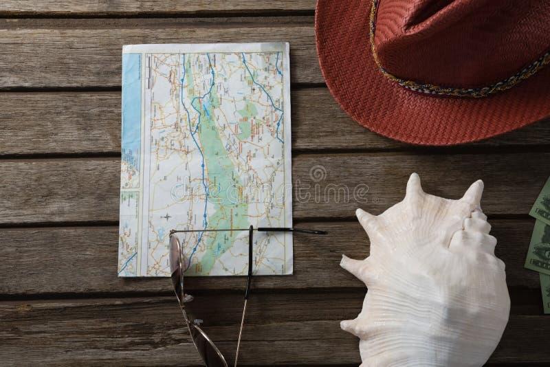 Mapa, kapelusz, seashell i widowiska na drewnianej desce, zdjęcia stock