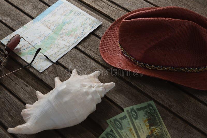 Mapa, kapelusz, seashell, walut notatki i okulary przeciwsłoneczni na drewnianej desce, obrazy stock