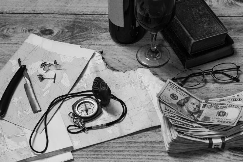 Mapa, kompas, wino, pieniądze, książki, brzytwa, spinki do mankietów, wiązanie i okulary, czarne i białe, poziome fotografia stock