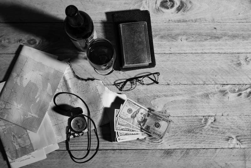 Mapa, kompas, wino, pieniądze, książki i okulary, czarny i biały zdjęcia royalty free