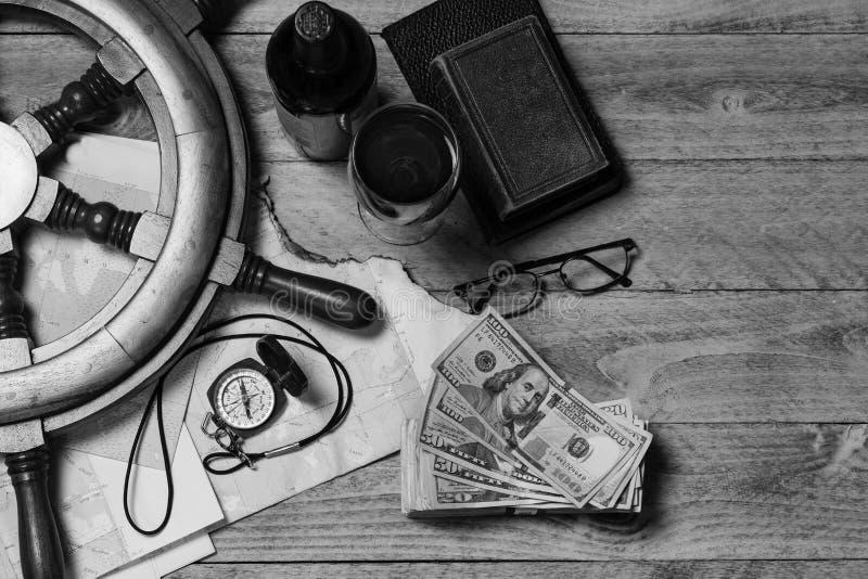 Mapa, kompas, wino, pieniądze, książki, koło okrętowe i okulary, czarny i biały fotografia stock