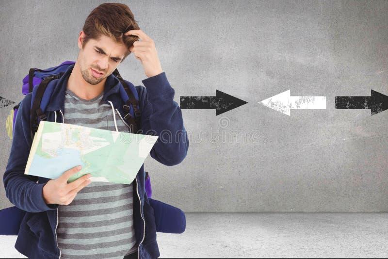 Mapa masculino confuso de la lectura del caminante mientras que se opone a flechas en fondo fotografía de archivo libre de regalías