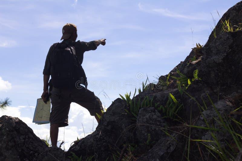 Mapa masculino joven de la tenencia de la mano del caminante con la mochila que se relaja en el top imagenes de archivo