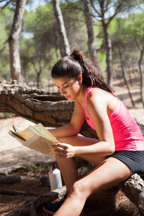 Mapa moreno novo da leitura da menina que senta-se no log fotografia de stock royalty free
