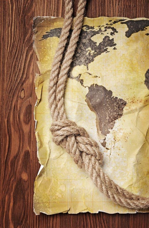 Mapa velho do vintage do mundo no papel manchado retro amarelo com nó da corda fotografia de stock