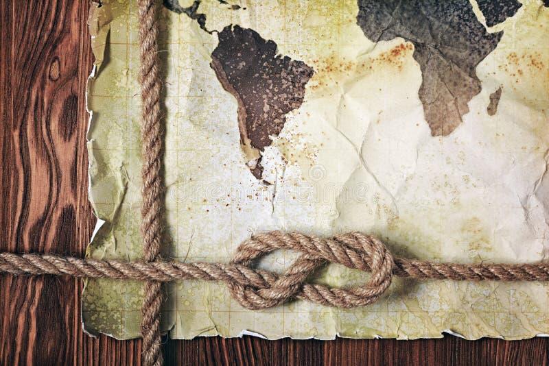 Mapa viejo del vintage del mundo en el papel manchado retro amarillo con el nudo de la cuerda fotografía de archivo