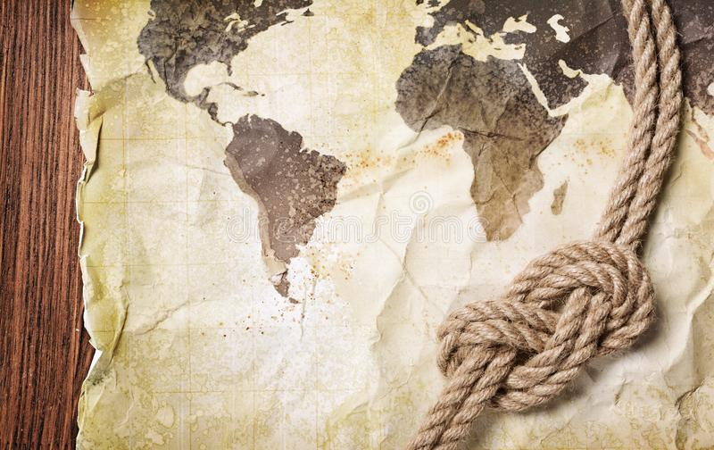 Mapa viejo del vintage del mundo en el papel manchado retro amarillo con el nudo de la cuerda imagen de archivo