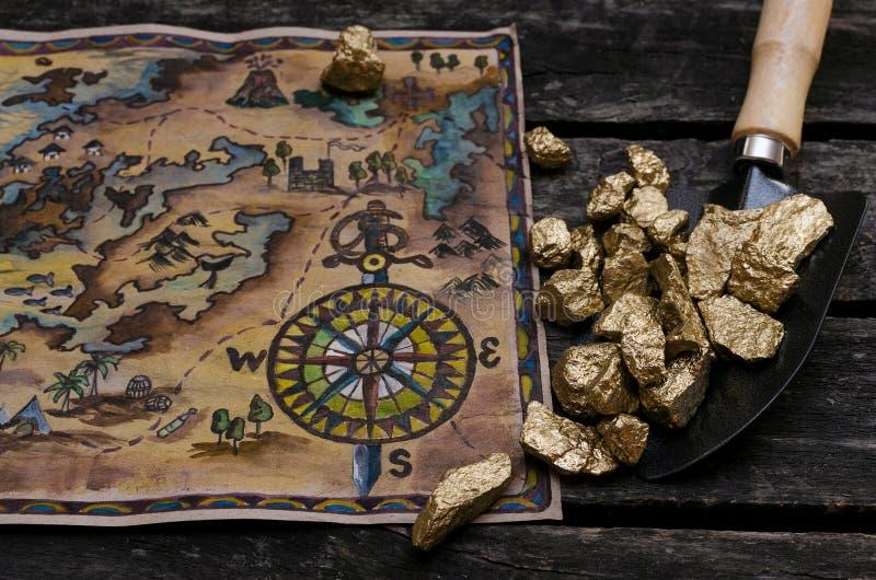 Mapa y oro del tesoro foto de archivo