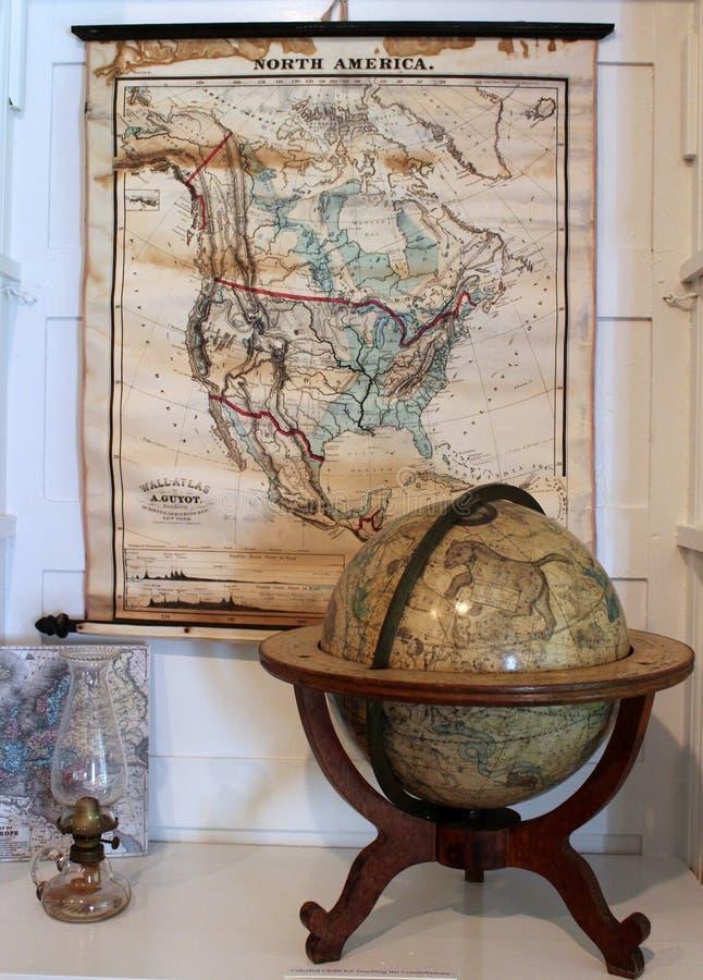 Mapas e globos com outros artigos históricos que descrevem a vida e as invenções em Oneida Community Mansion House, Oneida New Yo imagens de stock