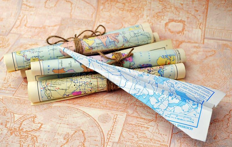 Mapas rodados viejos y aeroplano de papel fotografía de archivo libre de regalías
