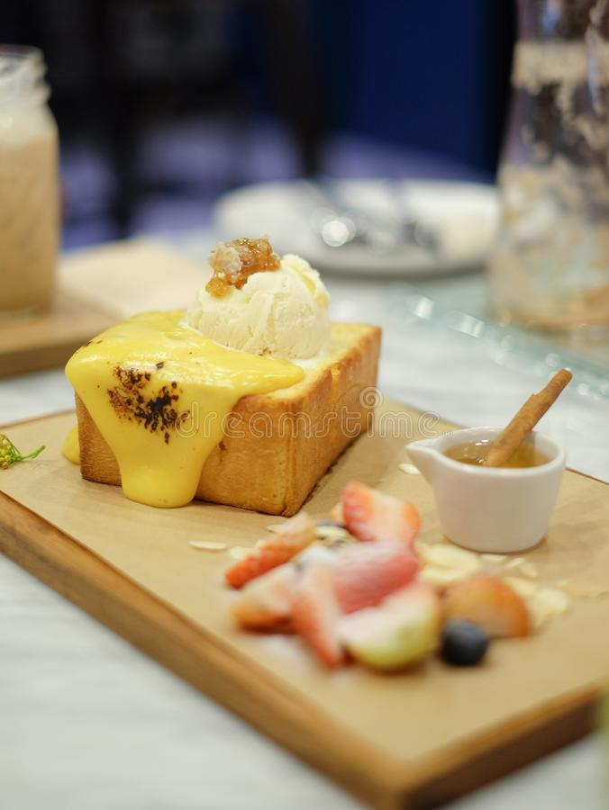 Maple custard brulee honey toast with vanilla ice cream and strawberries. royalty free stock image