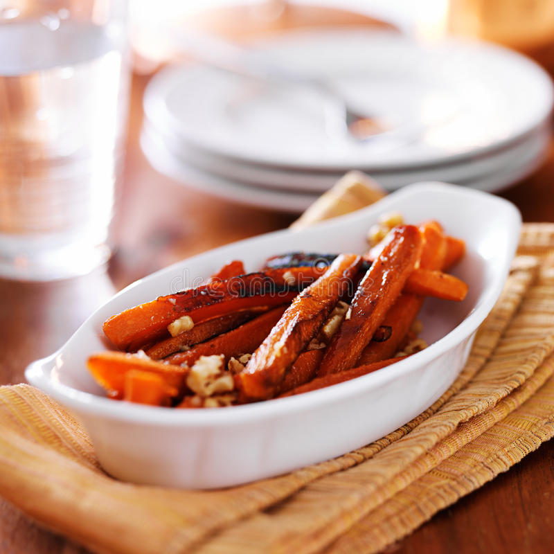 Maple glazed carrots with walnuts stock images