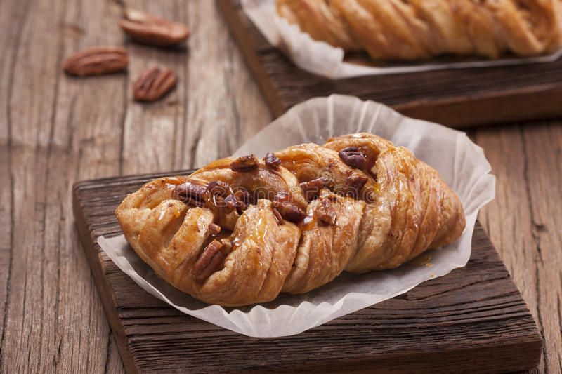 Maple pecan. Danish pastry maple pecan with nuts and maple syrup royalty free stock image
