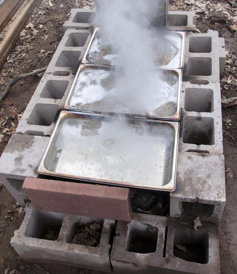 Maple sap concentrations boiling down to sweet homemade syrup in backyard evaporator. System made of stainless steel pans heated over fire in cinder blocks stock photography