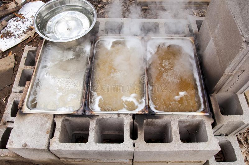 Maple sap concentrations boiling down to sweet homemade syrup in backyard evaporator. System made of stainless steel pans heated over fire in cinder blocks stock image