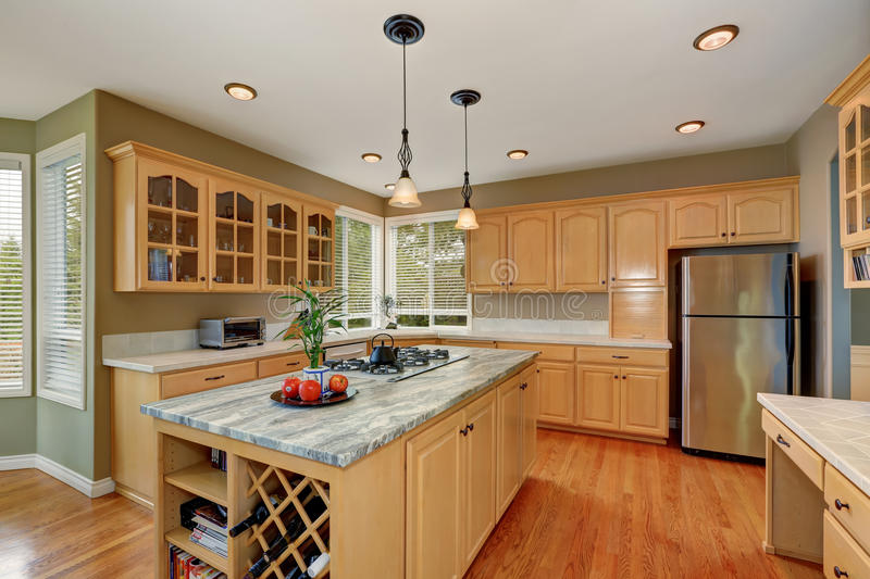 Maple storage combination and large island in the kitchen room stock photo