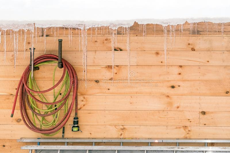 Maple sugar house with snow and icicles dripping off roof with red and green tubing hoses stock photos