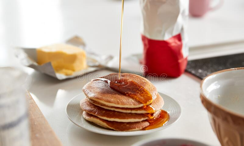 Maple Syrup Being Poured On Stack Of Freshly Made Pancakes Or Crepes On Table For Pancake Day stock photo