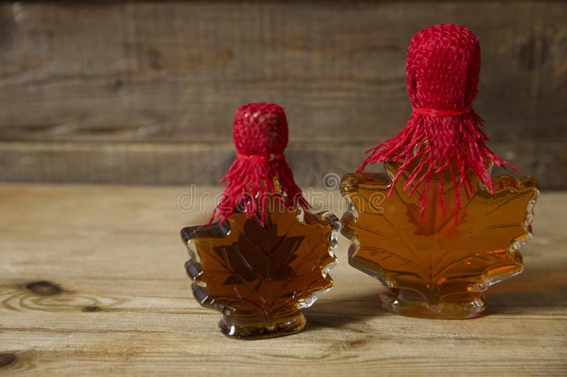 Maple syrup in a glass bottle in the form of a maple leaf on a wooden rustic background with copy space for text stock photo