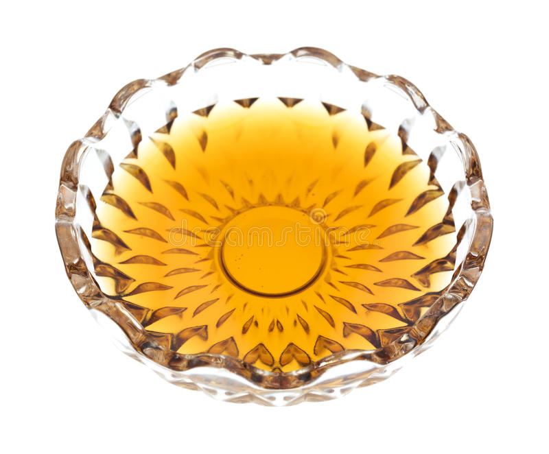 Maple syrup in a small bowl. Side view of a clear glass bowl with a portion of maple syrup on a white background stock photography
