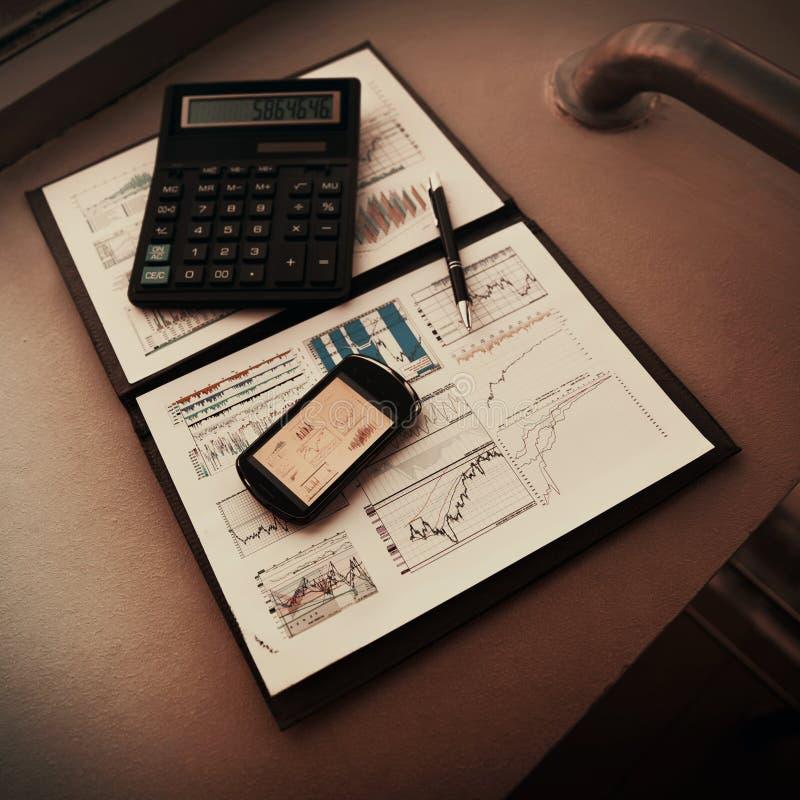 Mapp med diagrammen av finansiell analys Diagram i skärmen för telefon` s, är därefter räknemaskinen och pennan royaltyfria foton