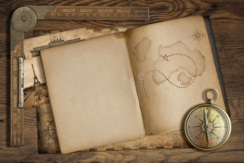 Mappa d'annata del tesoro in libro aperto con la bussola ed il vecchio righello royalty illustrazione gratis
