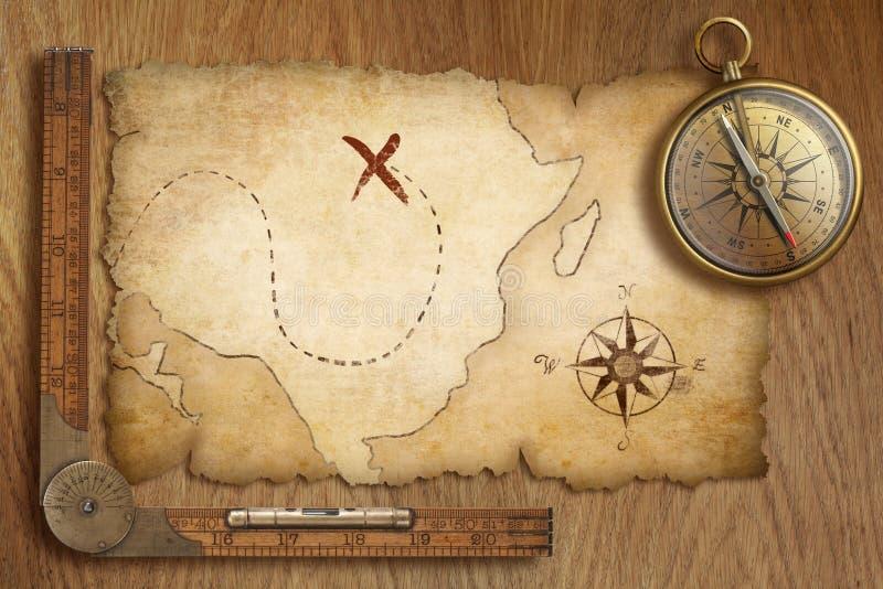 Mappa del tesoro, righello e bussola invecchiati del vecchio oro sulla tavola di legno illustrazione di stock
