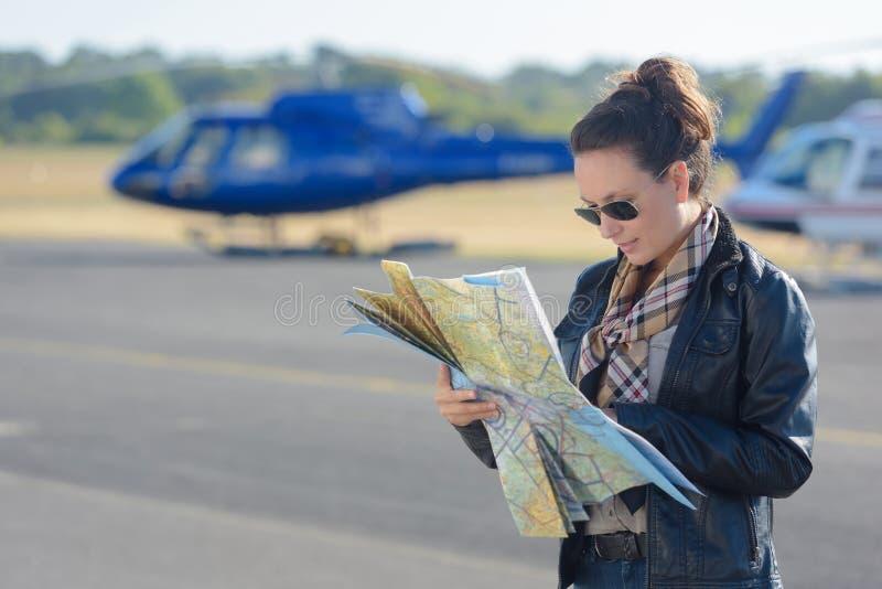 Mappa della lettura del pilota dell'elicottero della donna fotografia stock
