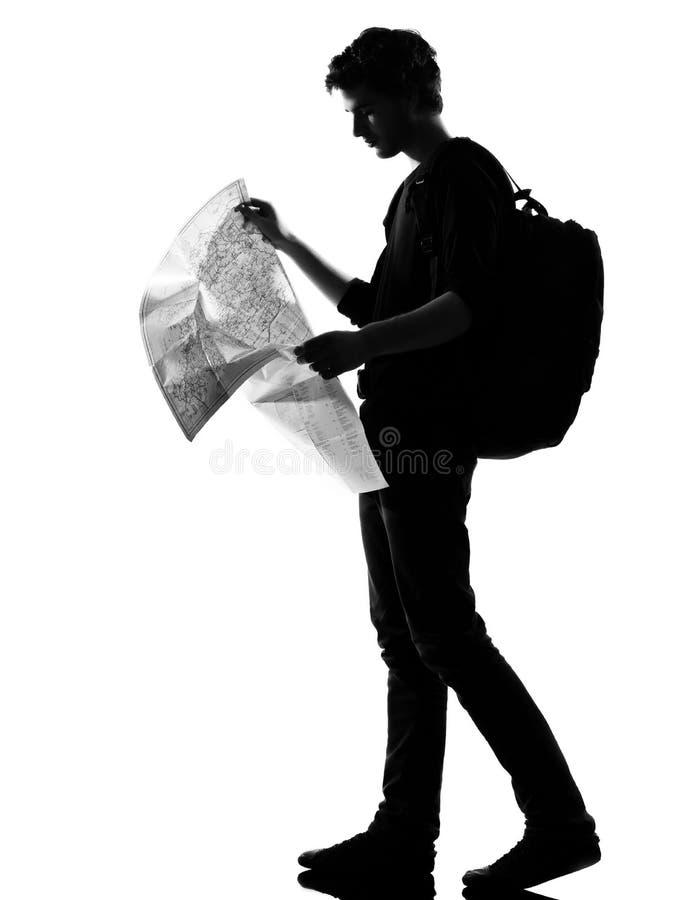 Mappa della lettura di viaggiatore con zaino e sacco a pelo della siluetta del giovane immagine stock libera da diritti