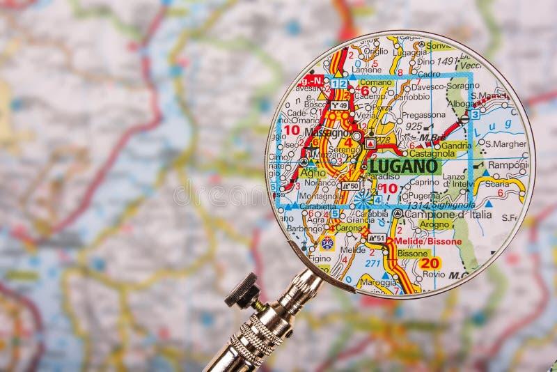 Mappa di Lugano con la lente d'ingrandimento sulla tavola fotografia stock