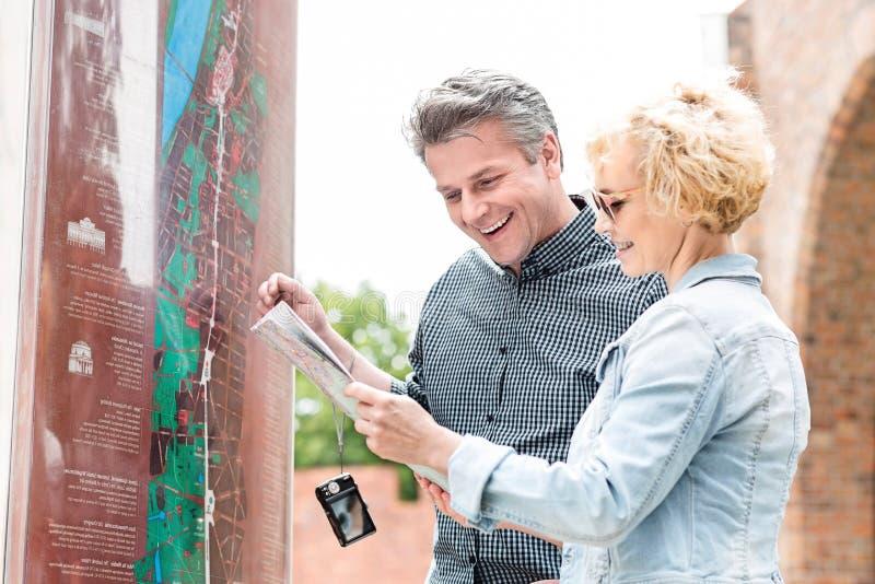 Mappa di mezza età allegra della lettura delle coppie in città immagine stock libera da diritti