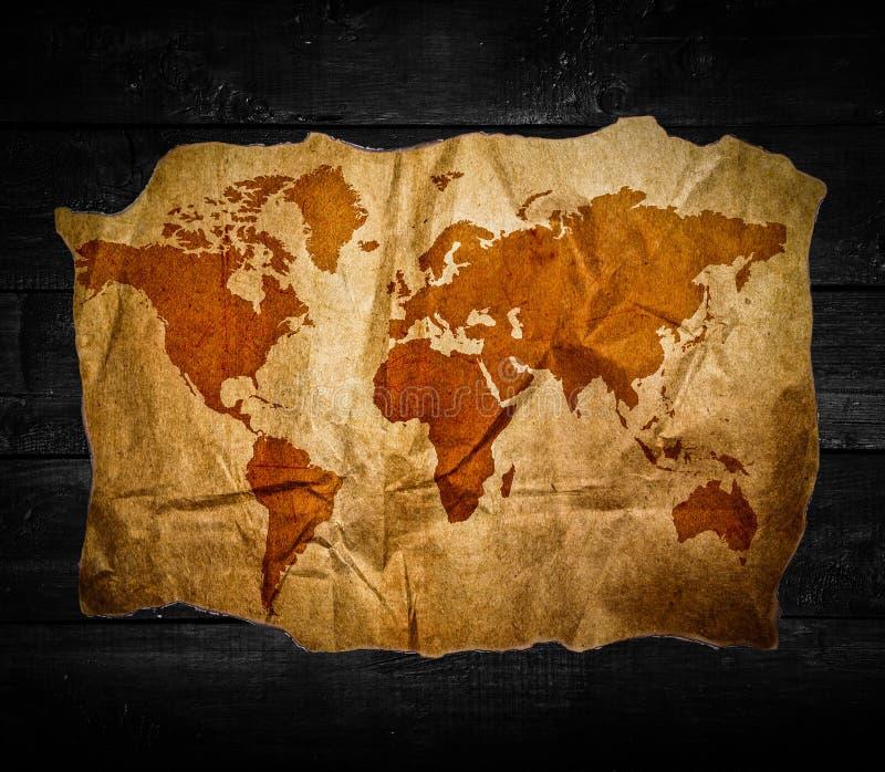 Mappa di mondo antica nel fondo di legno nero fotografie stock