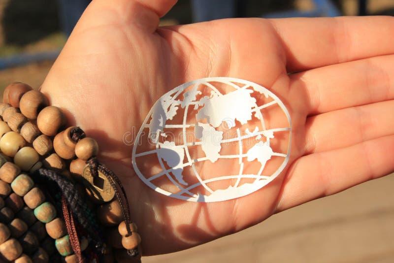 Mappa di mondo simbolica nelle mani della ragazza di hippy immagini stock