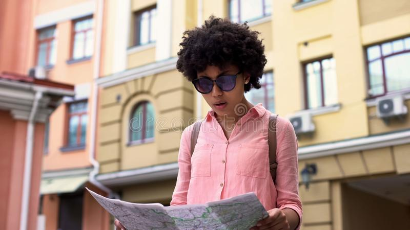Mappa di sguardo turistica abbastanza femminile, cercante i posti facenti un giro turistico della città, viaggio fotografia stock