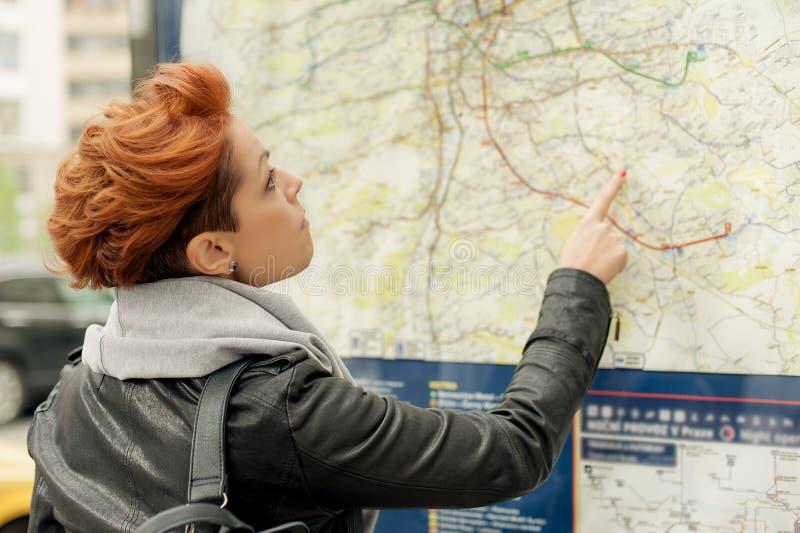 Mappa stradale pubblica di sguardo turistica femminile fotografie stock libere da diritti