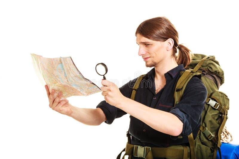 Mappa turistica della lettura dell'uomo con la lente d'ingrandimento fotografia stock libera da diritti